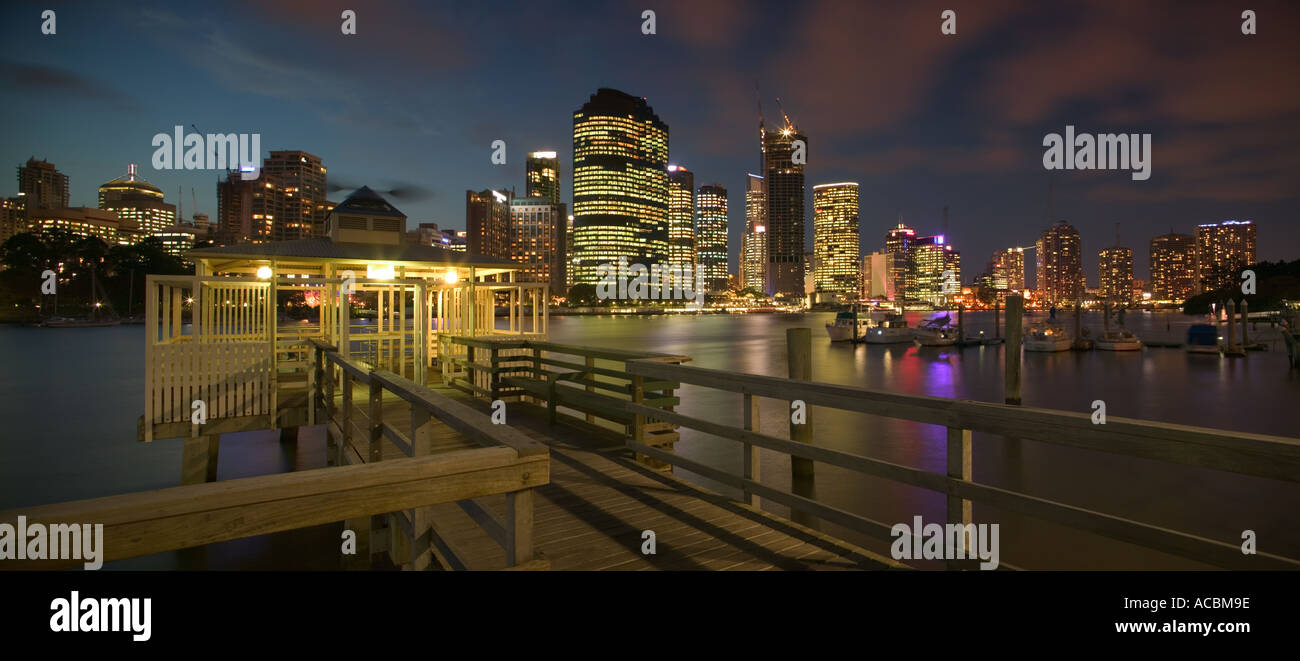 View of the CBD across the Brisbane River at dusk. - Stock Image