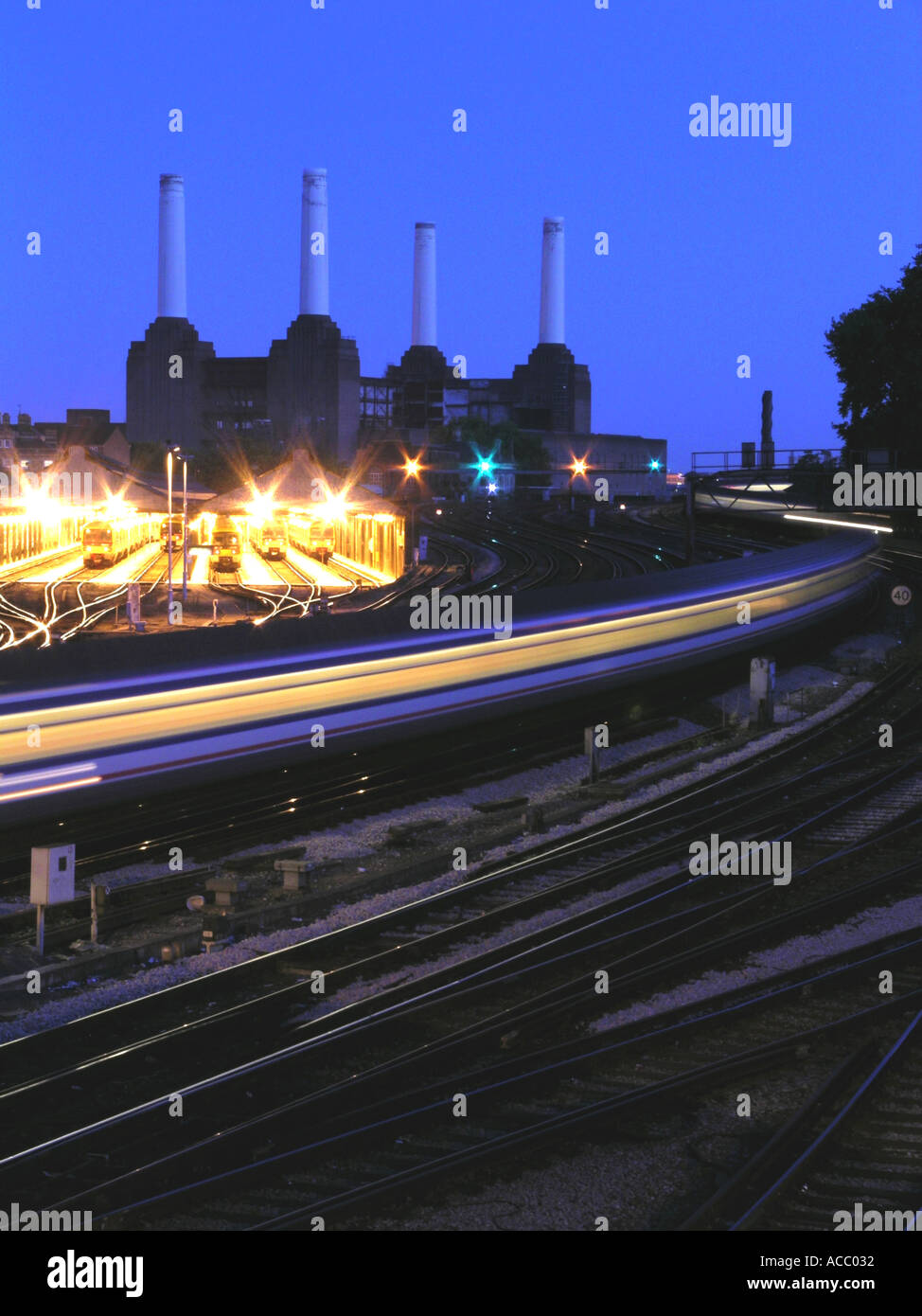 Train from Victoria Station passing the now disused Battersea Power Station in London England UK dusk night - Stock Image