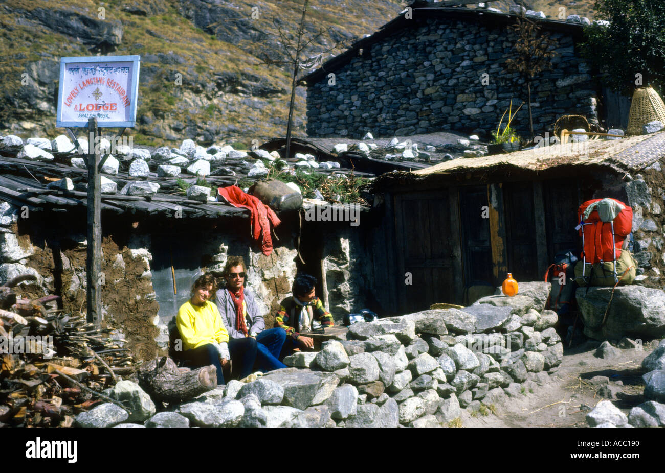 Two hikers rest outside a trekking lodge teahouse Langtang Valley Nepal - Stock Image