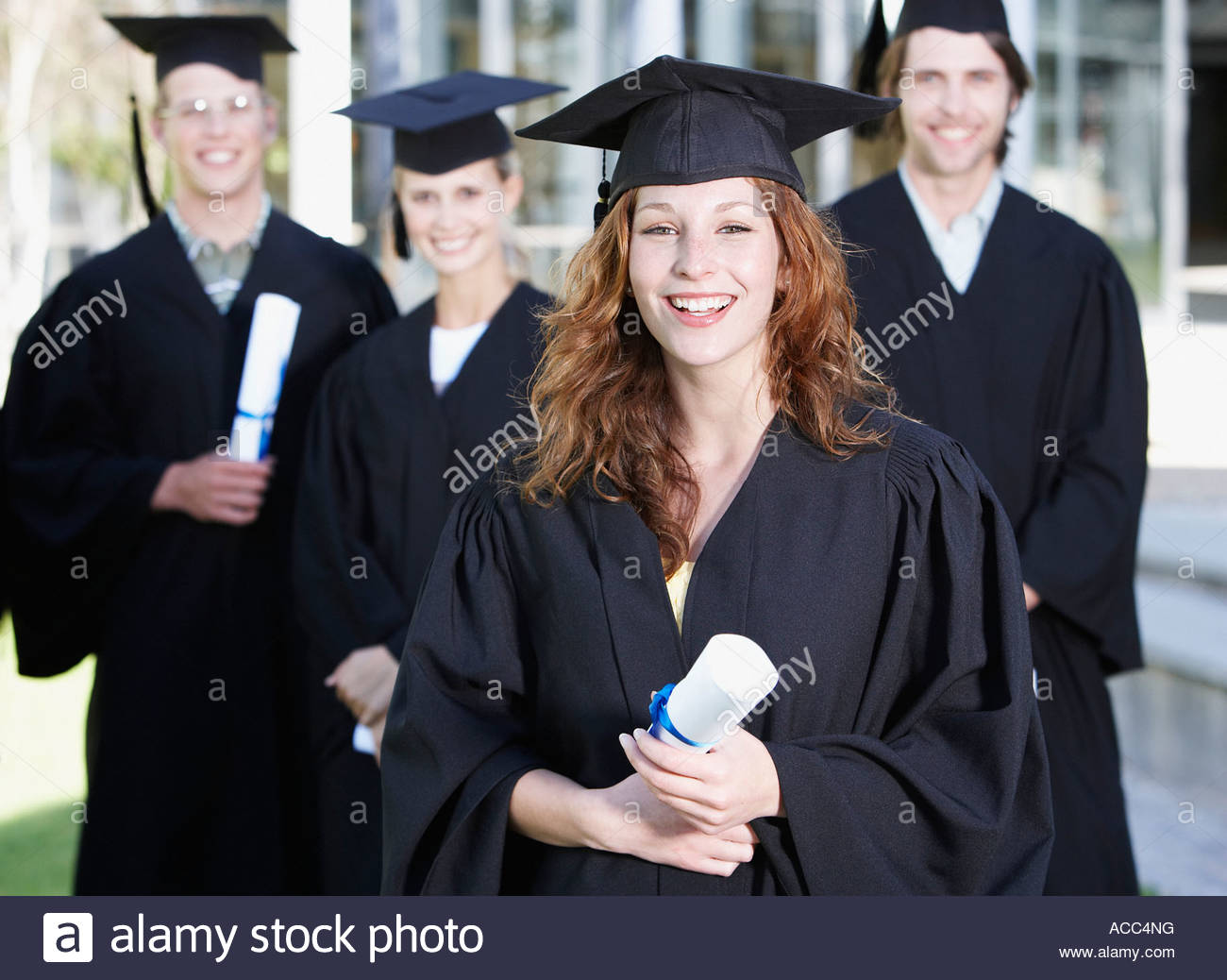 Teenagers in graduation gowns and mortar boards with diplomas - Stock Image