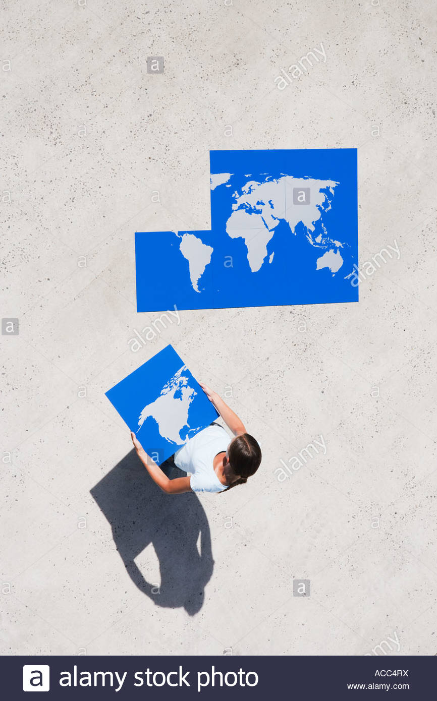 Aerial View of woman with piece of world map puzzle outdoors - Stock Image