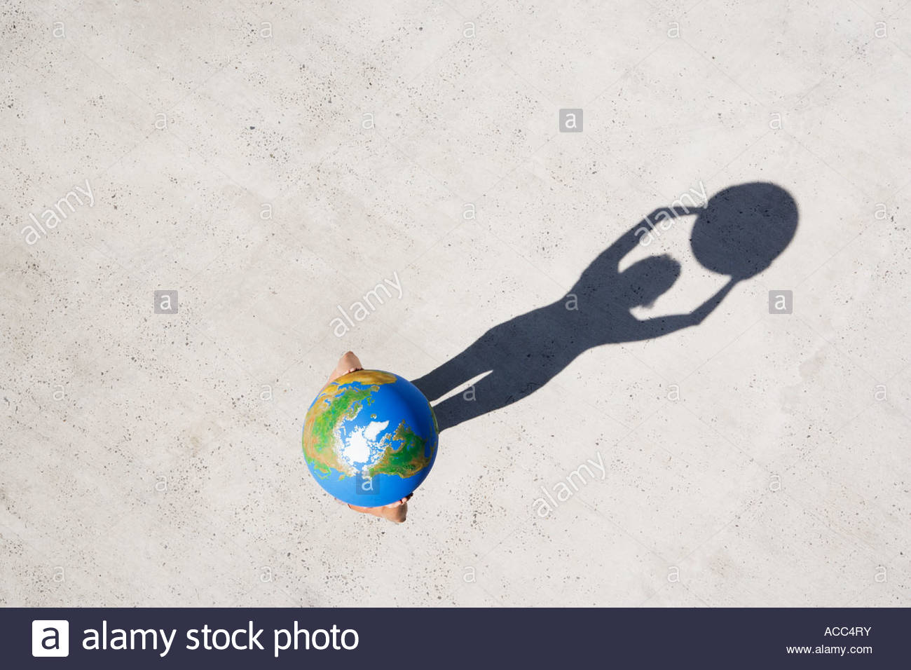 Aerial View of person holding globe above head with shadow - Stock Image