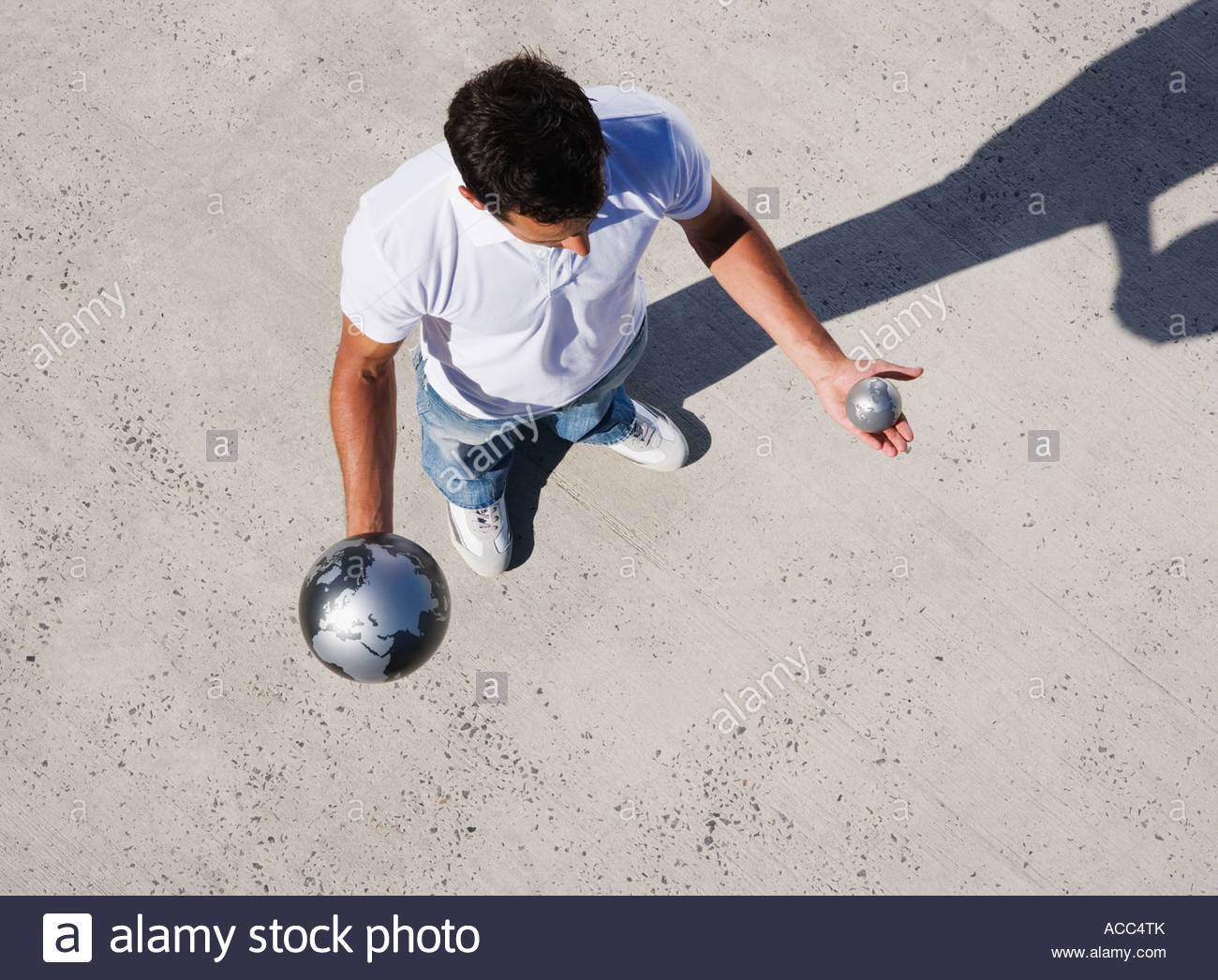 Aerial View of man holding large and small globes outdoors - Stock Image