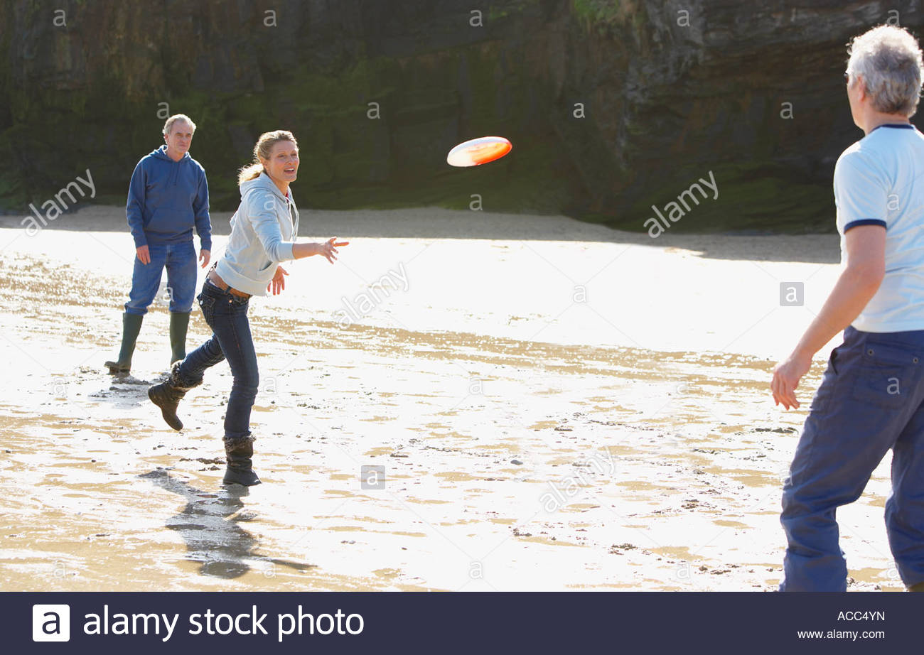 Three adults playing Frisbee on the beach - Stock Image