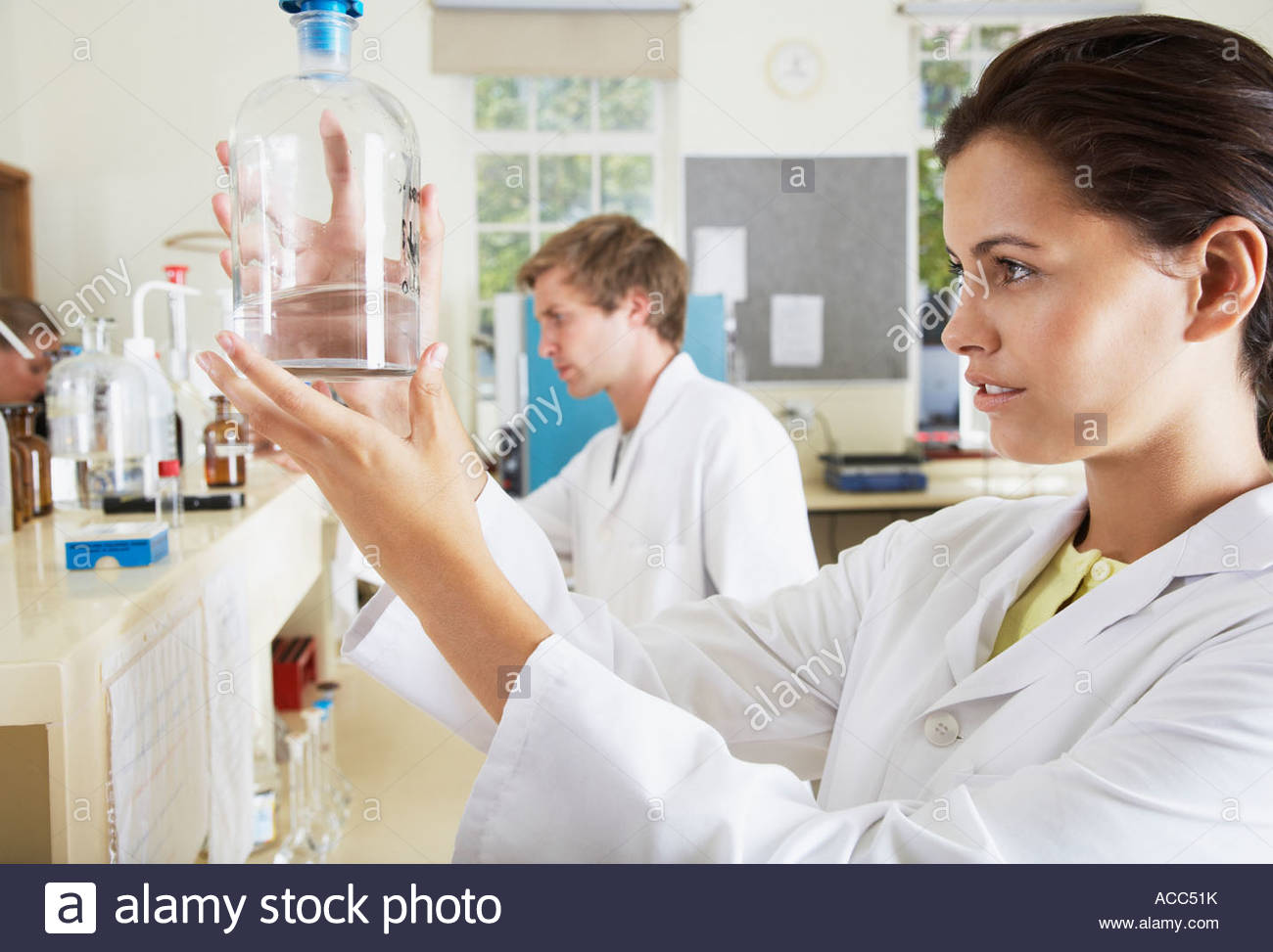 Woman in a laboratory measuring a liquid with one man in the background - Stock Image
