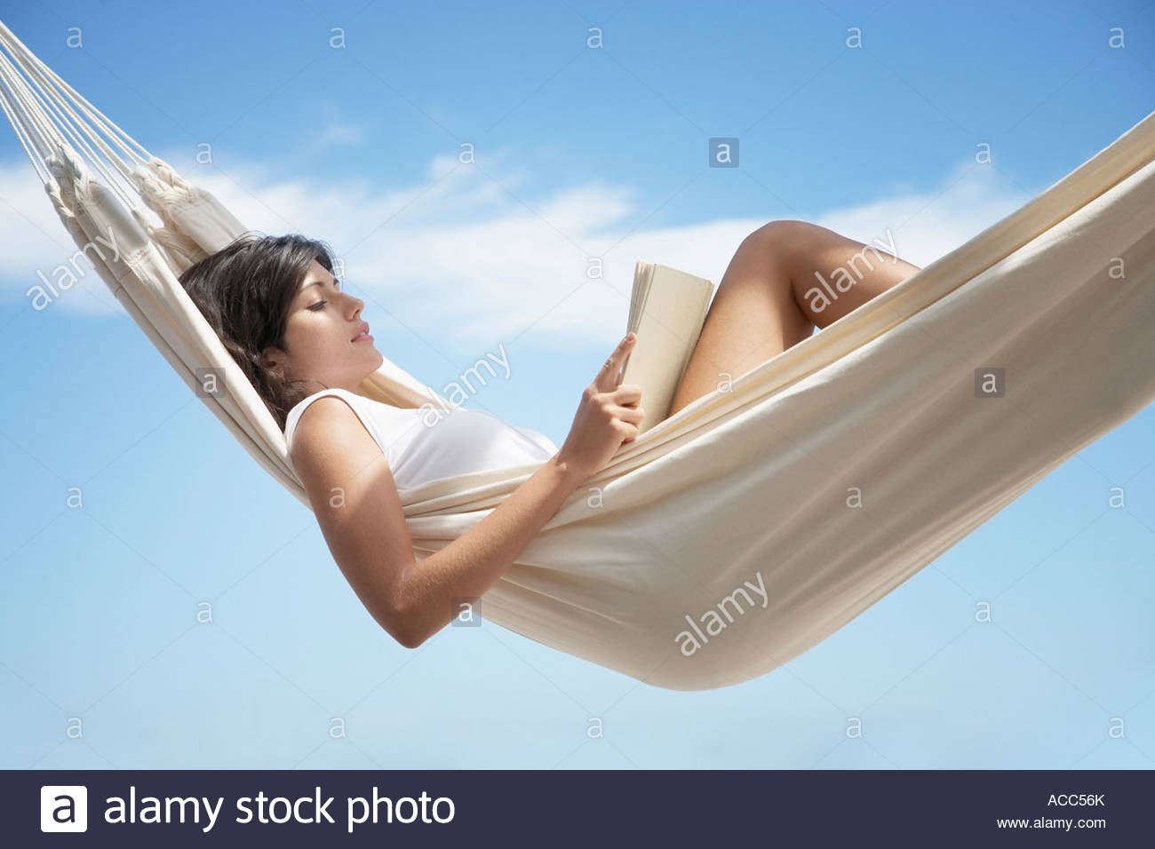Woman reading in a hammock - Stock Image