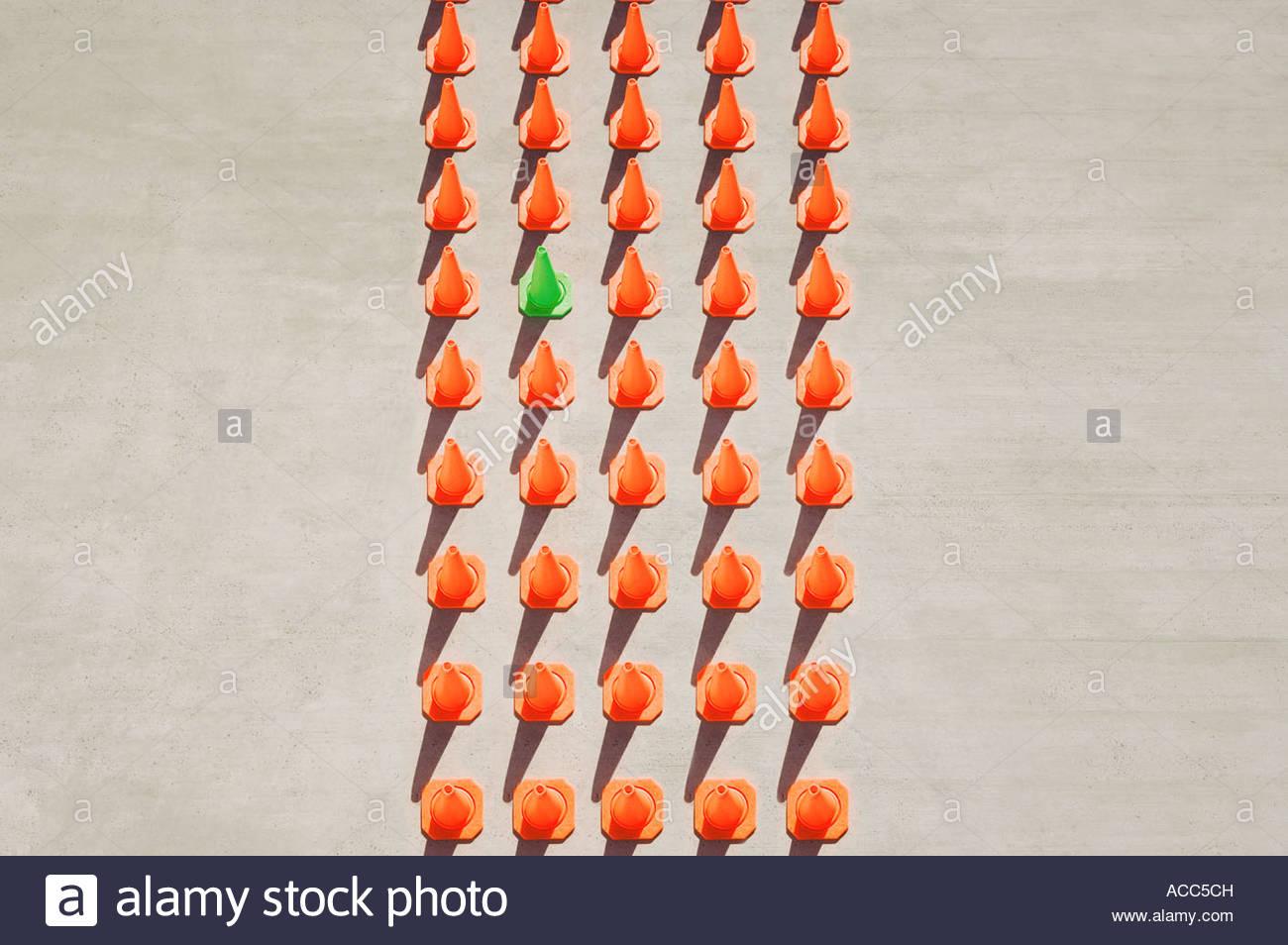 One green pylon amid forty-four orange pylons - Stock Image