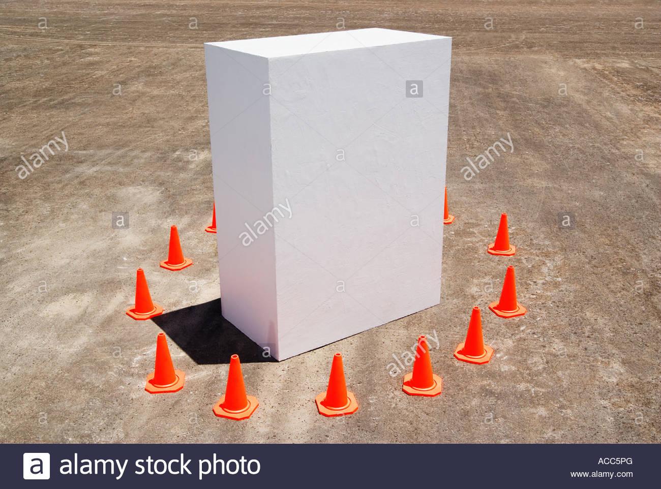 Traffic cones around white box - Stock Image