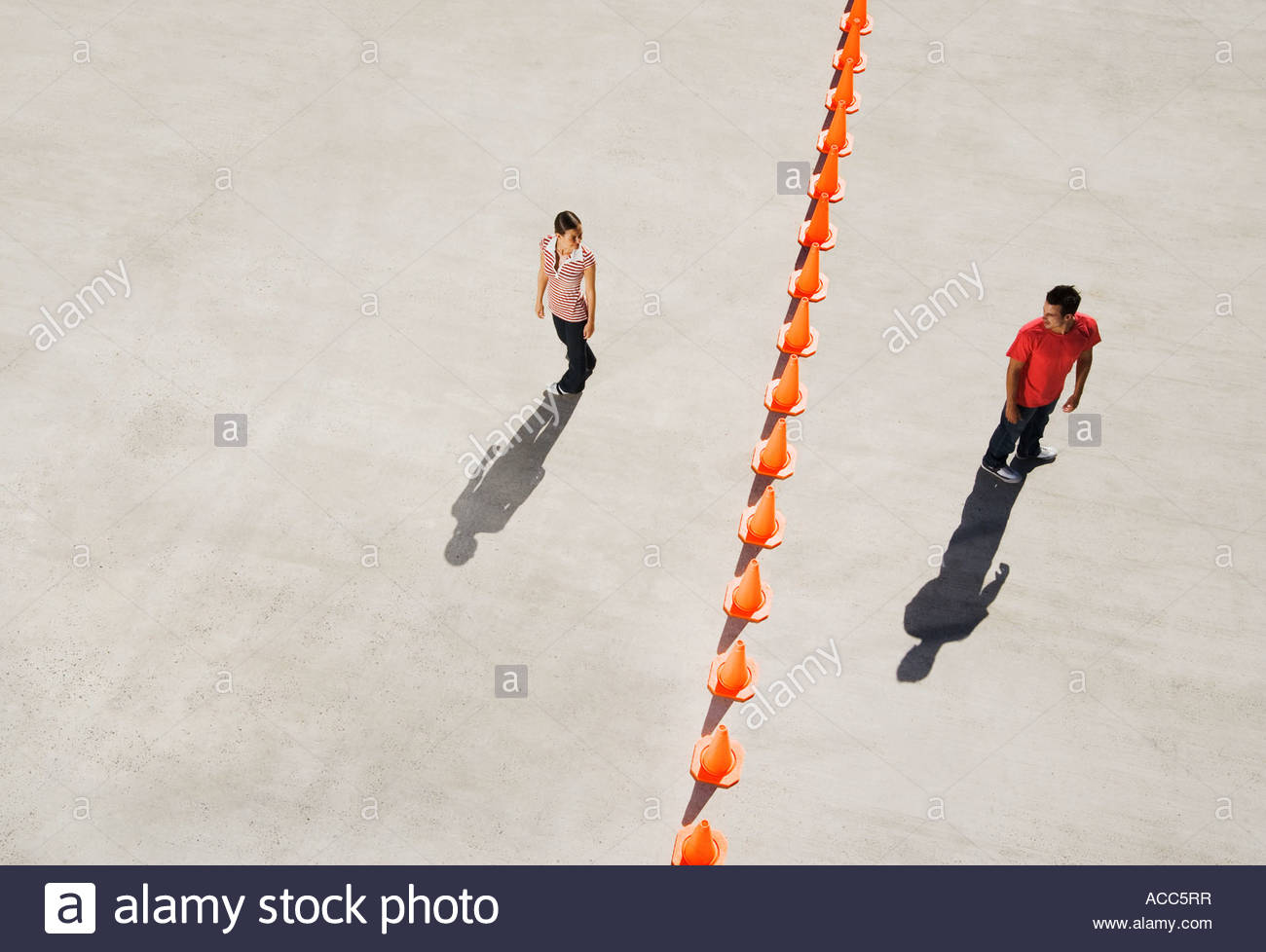 Man and woman on either side of row of traffic cones looking back Stock Photo