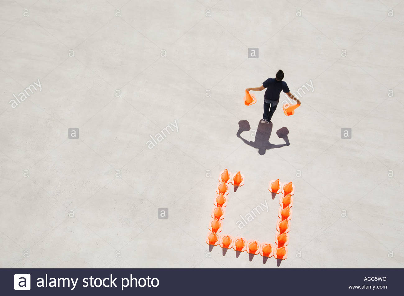 Man walking away from box of traffic cones with two - Stock Image