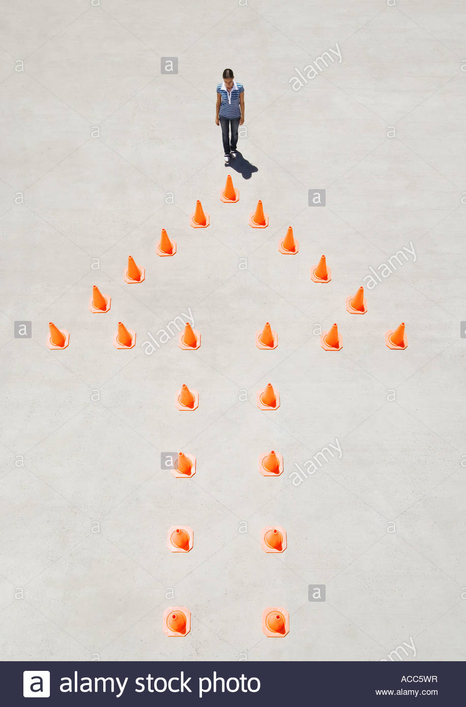 Traffic cones forming arrow with woman at top - Stock Image