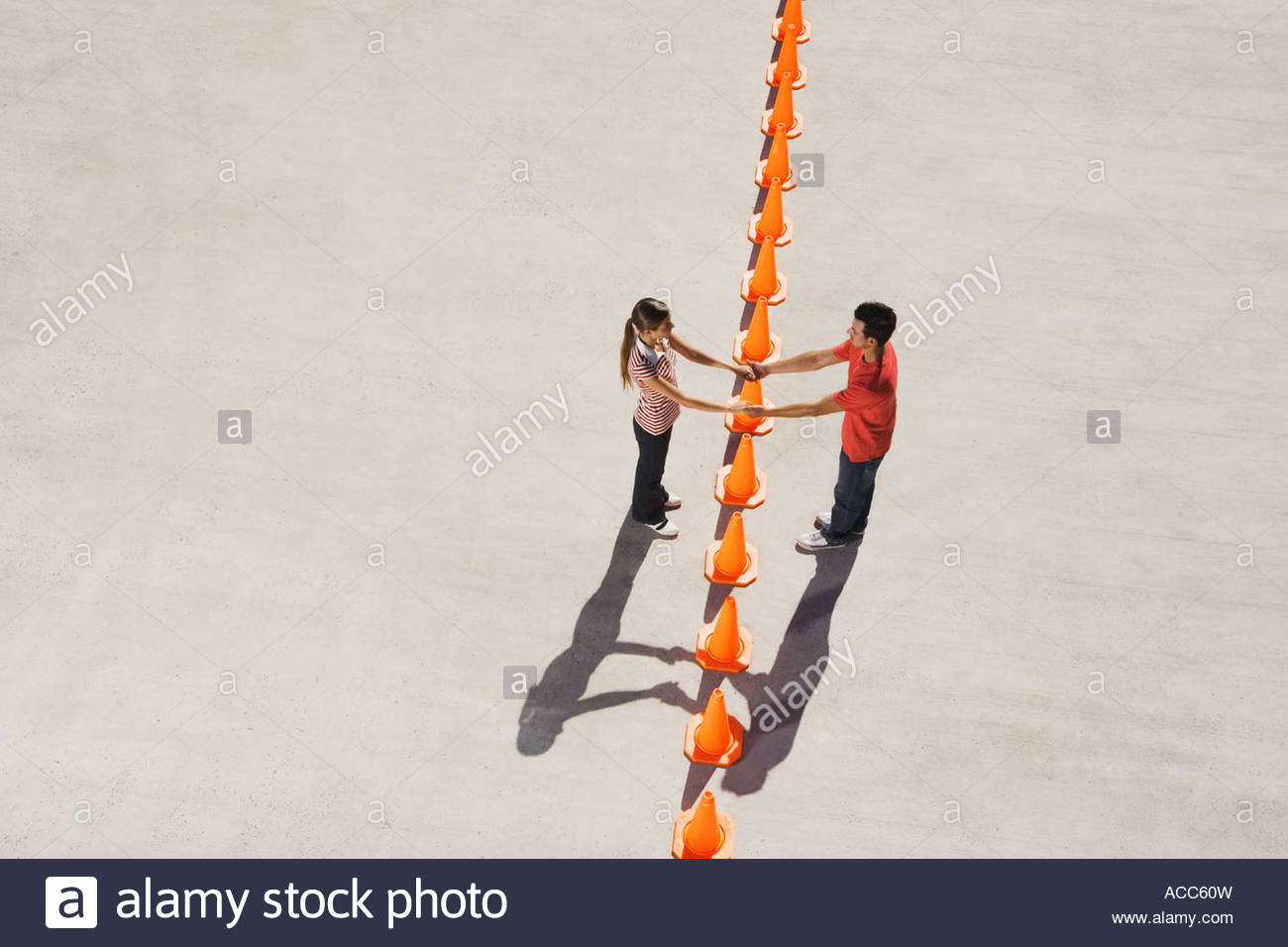 Man and woman holding hands over row of traffic cones - Stock Image