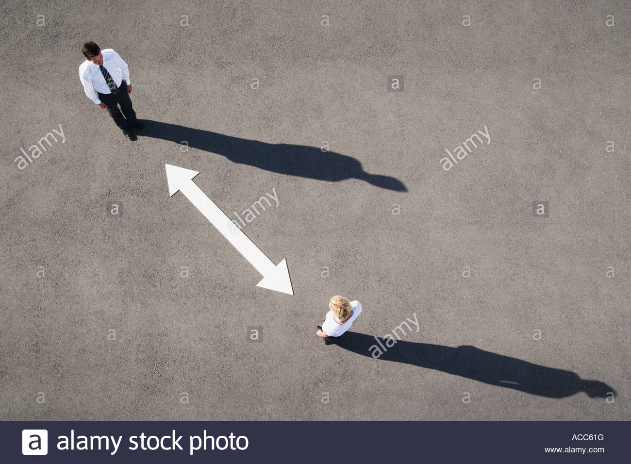 Aerial view of man and woman with arrow on pavement - Stock Image