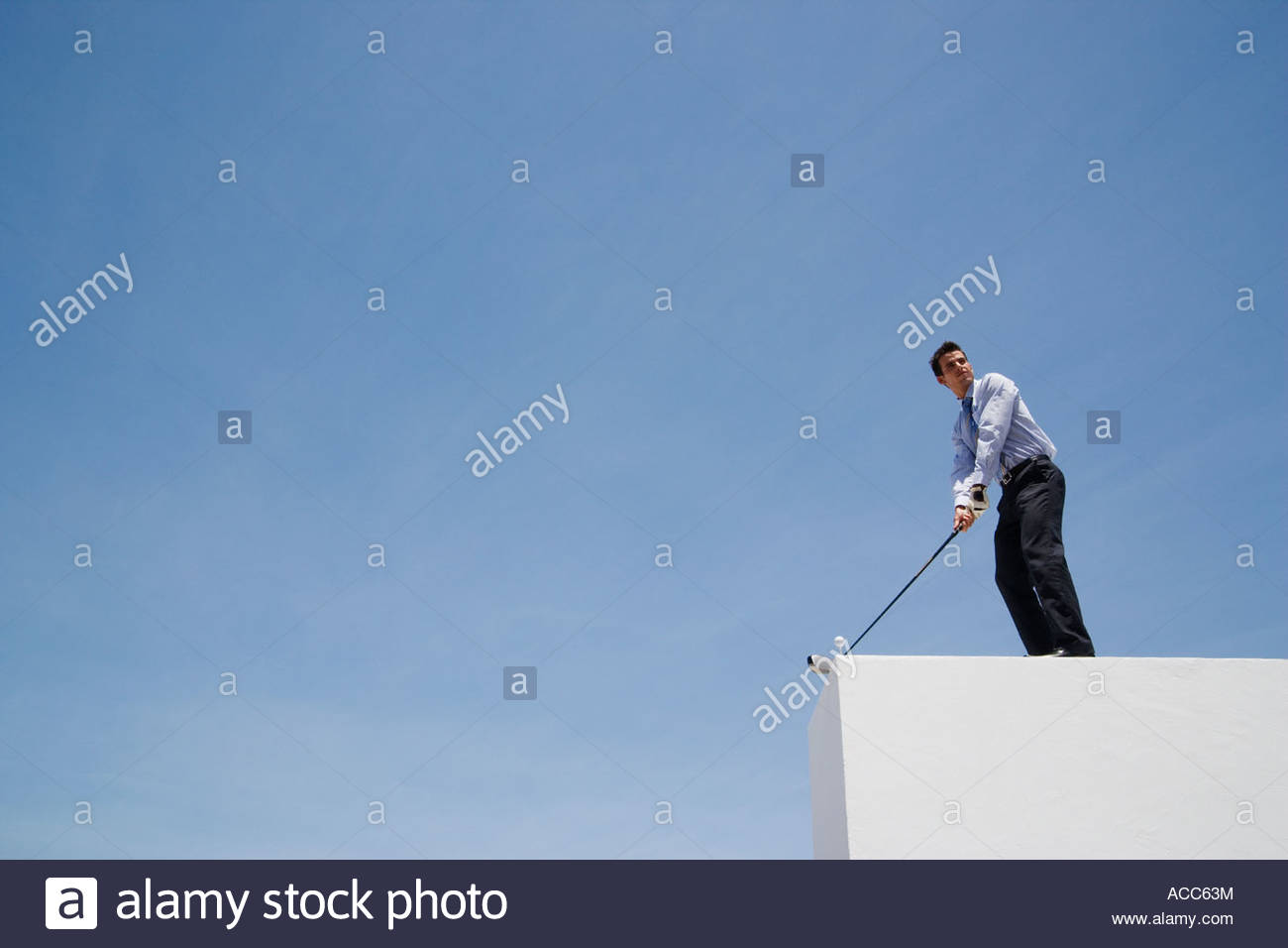Businessman golfing on roof - Stock Image