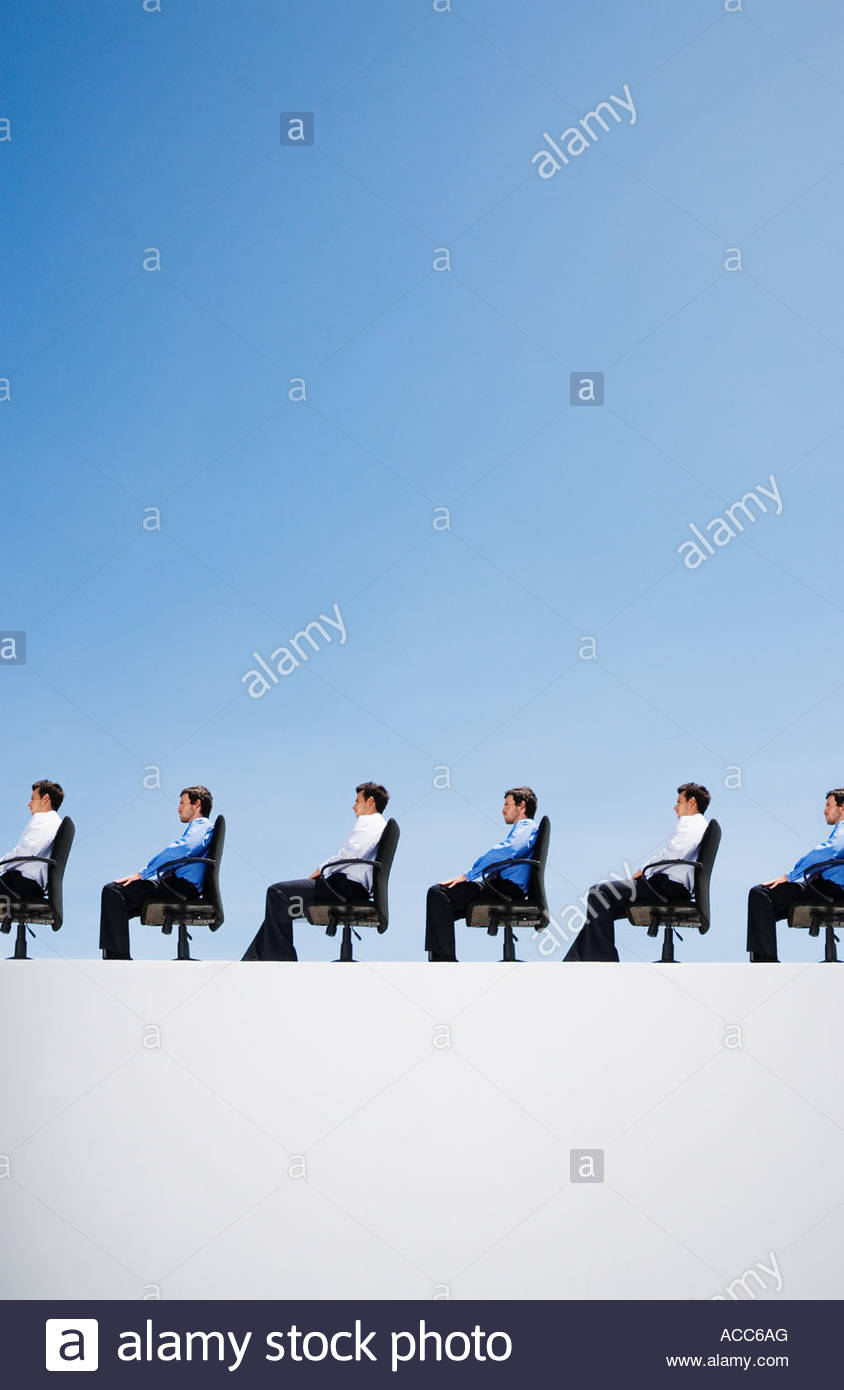Line-up of businessmen in their office chairs - Stock Image