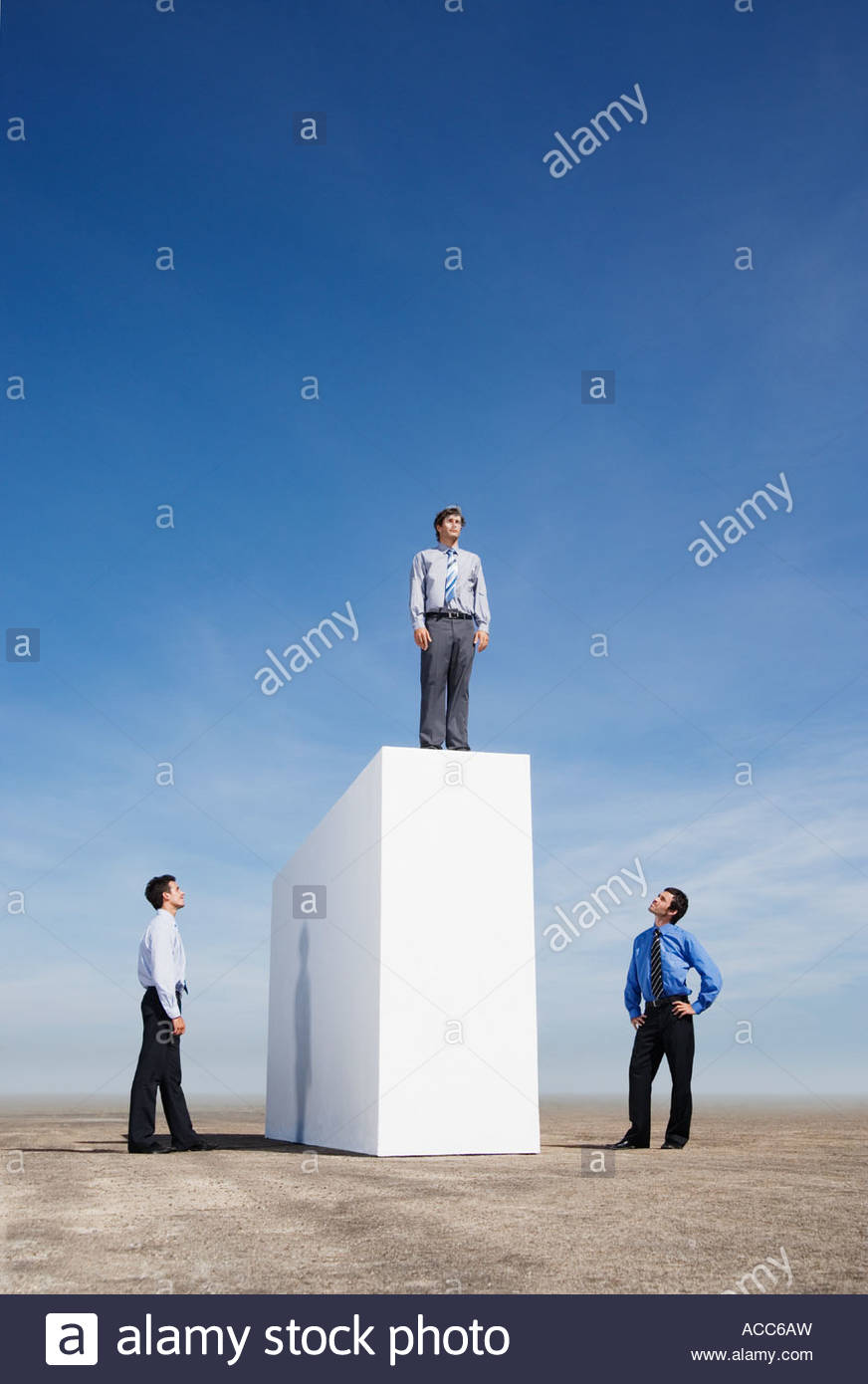 Businessman standing on wall outdoors with two men watching - Stock Image