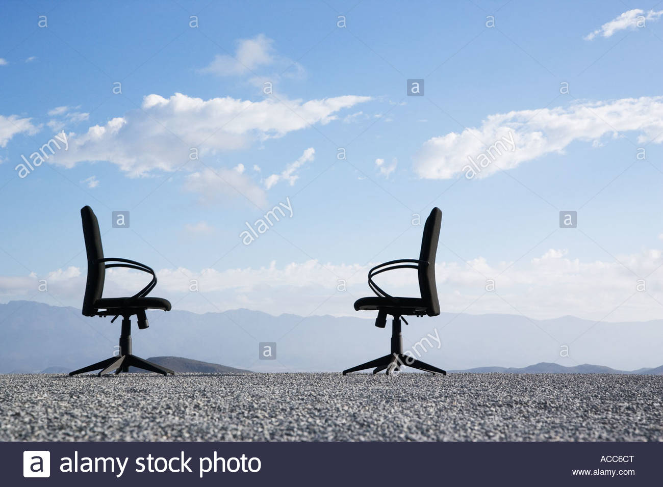 Two office chairs on a terrain full of pebbles - Stock Image