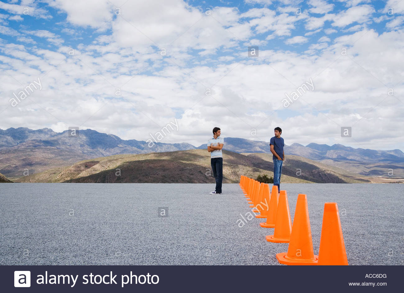 Two men divided by a row of safety cones - Stock Image