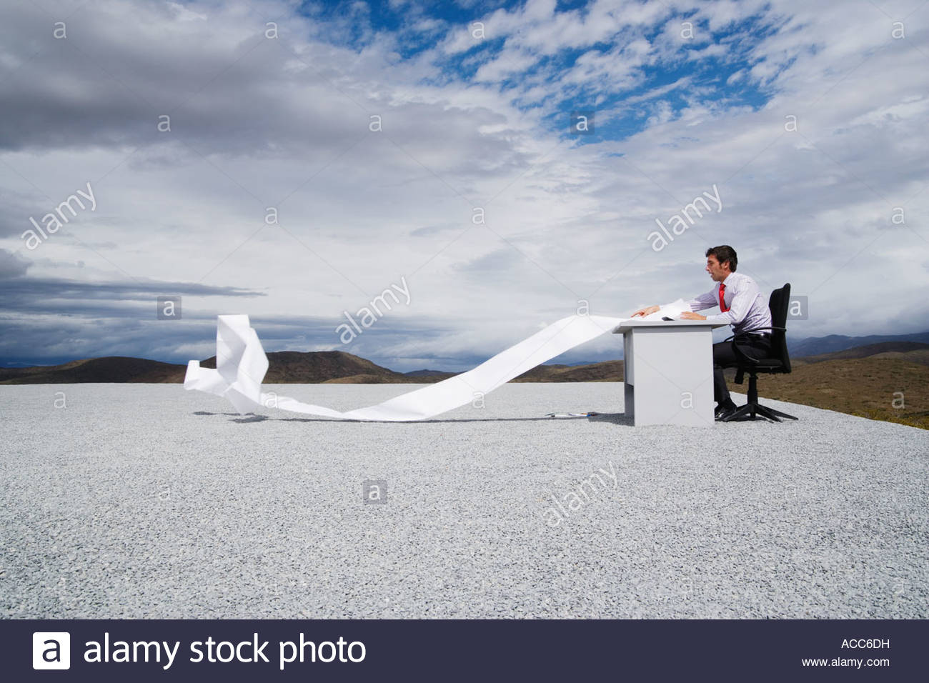 Man working outdoors with papers blowing in the wind - Stock Image