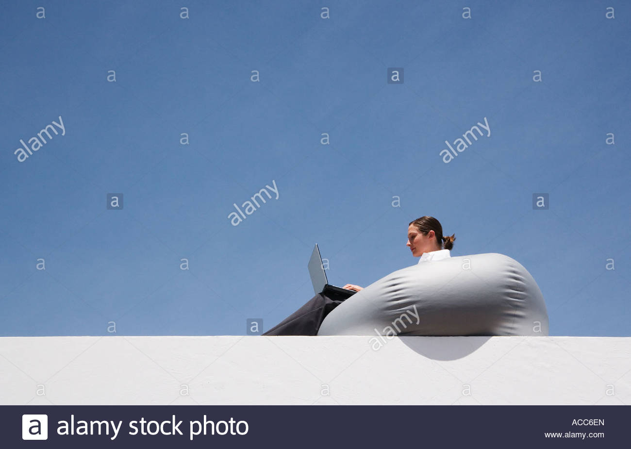 Businesswoman on beanbag chair with laptop outdoors - Stock Image