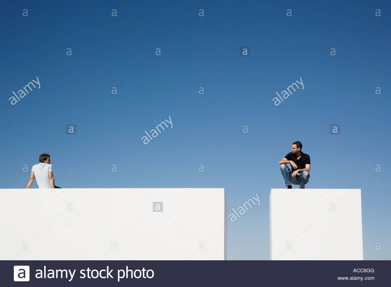 Man sitting on wall outdoors and man on pedestal - Stock Image