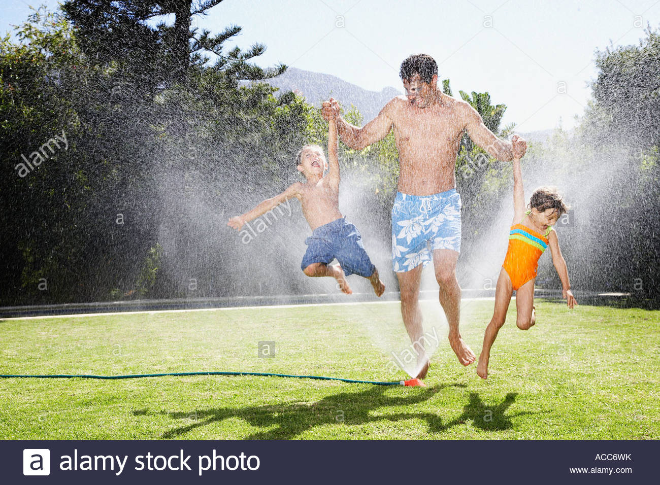 a father playing with his children in a sprinkler - Stock Image