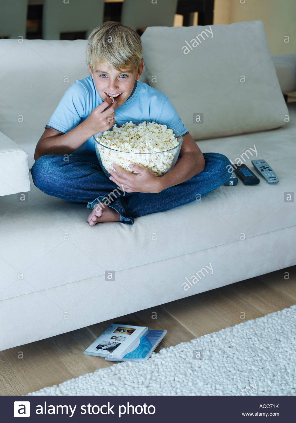 Young boy eating popcorn watching television - Stock Image