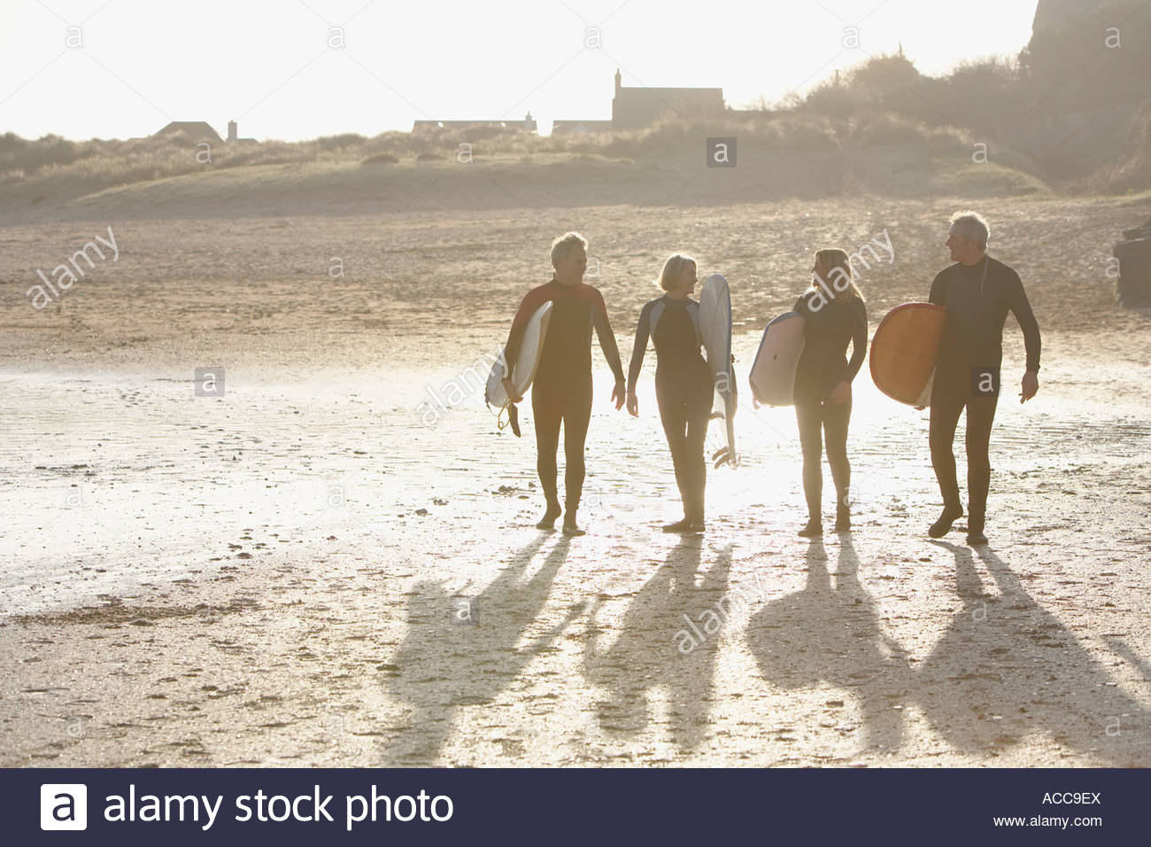 Four adults walking on the beach with surfboards - Stock Image