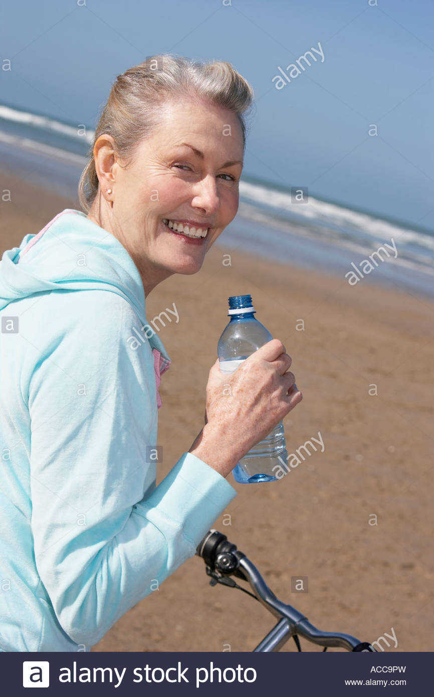 senior woman drinking water on a bike at the beach - Stock Image