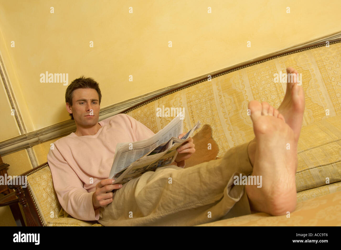 man reading a paper with his feet up on the sofa - Stock Image