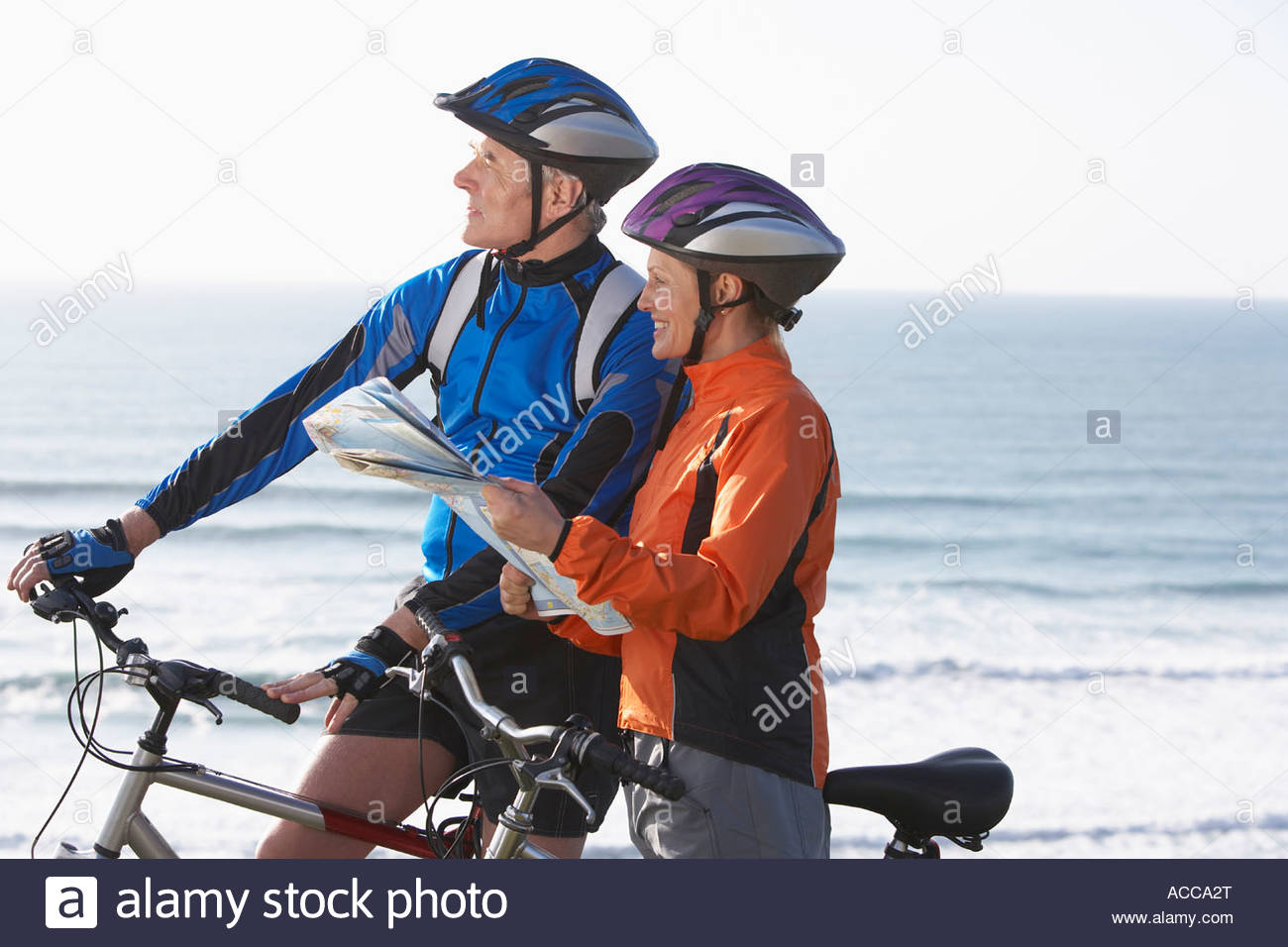 couple on bikes reading a map - Stock Image