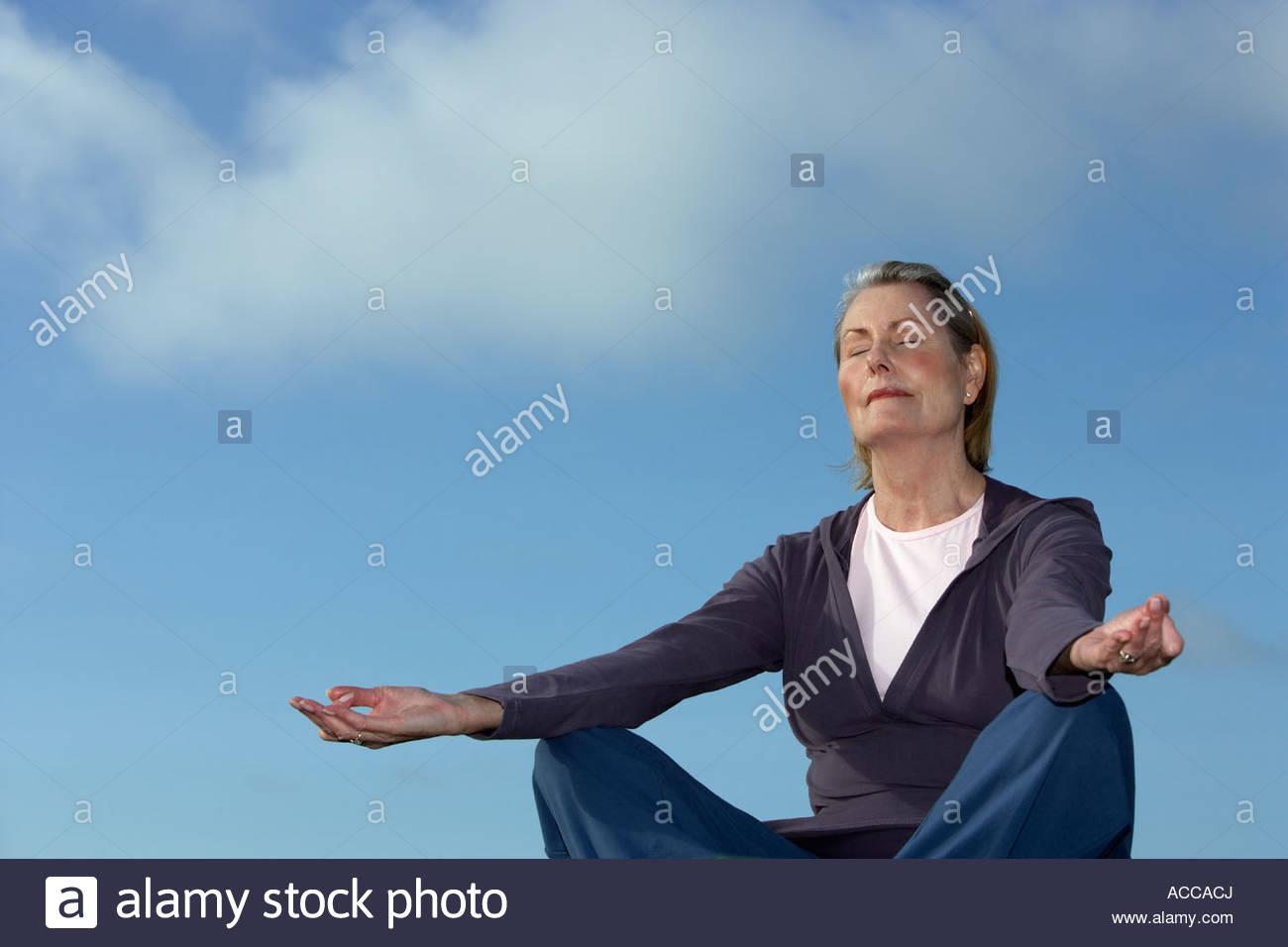 senior woman doing yoga outdoors - Stock Image