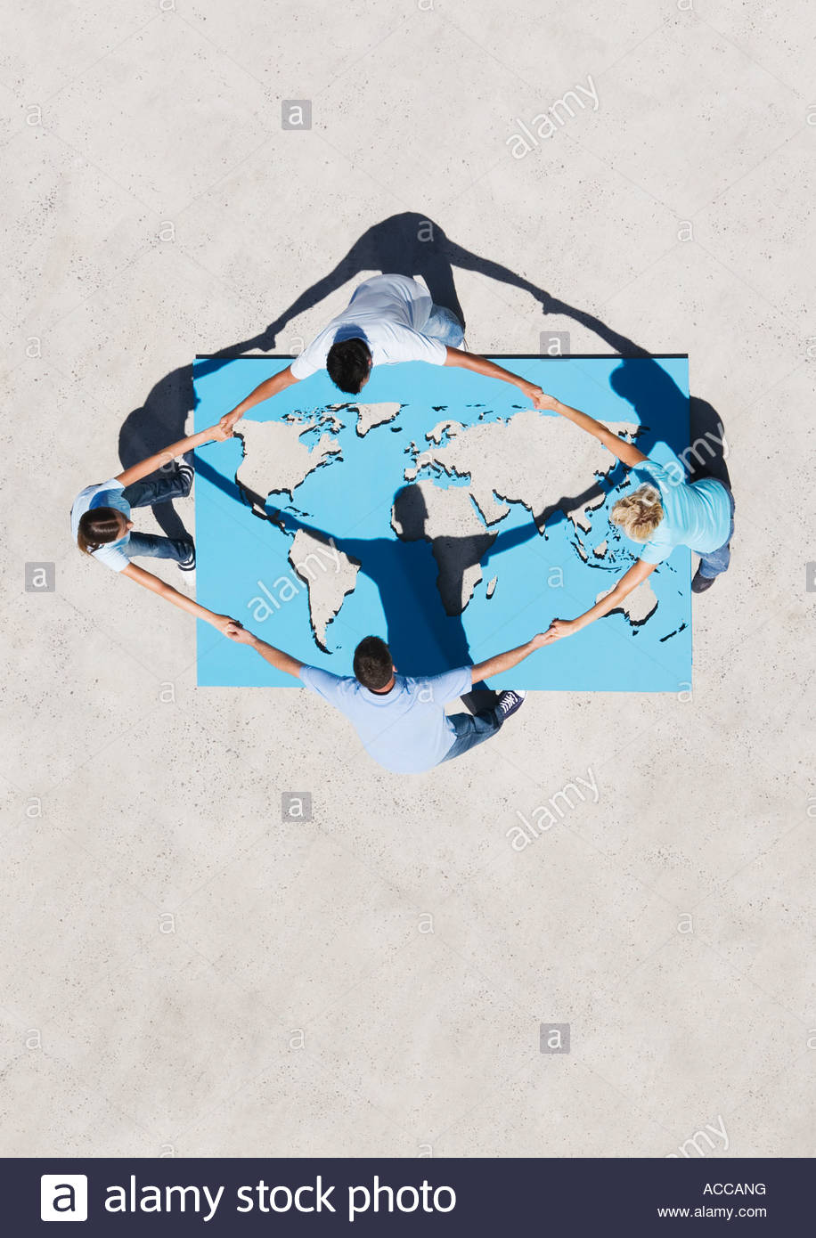 Four people holding hands above world map outdoors - Stock Image