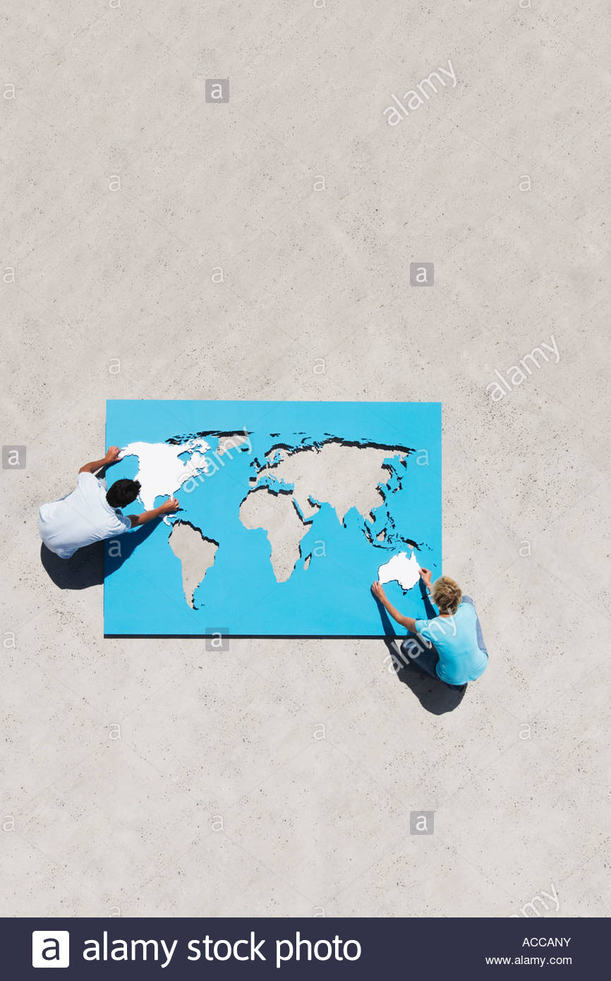 Aerial view of man and woman outdoors with world map puzzle - Stock Image