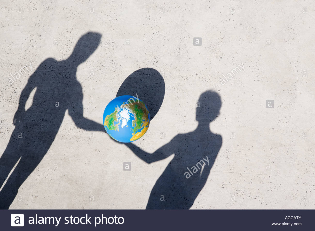 Aerial View of two shadows holding globe outdoors - Stock Image