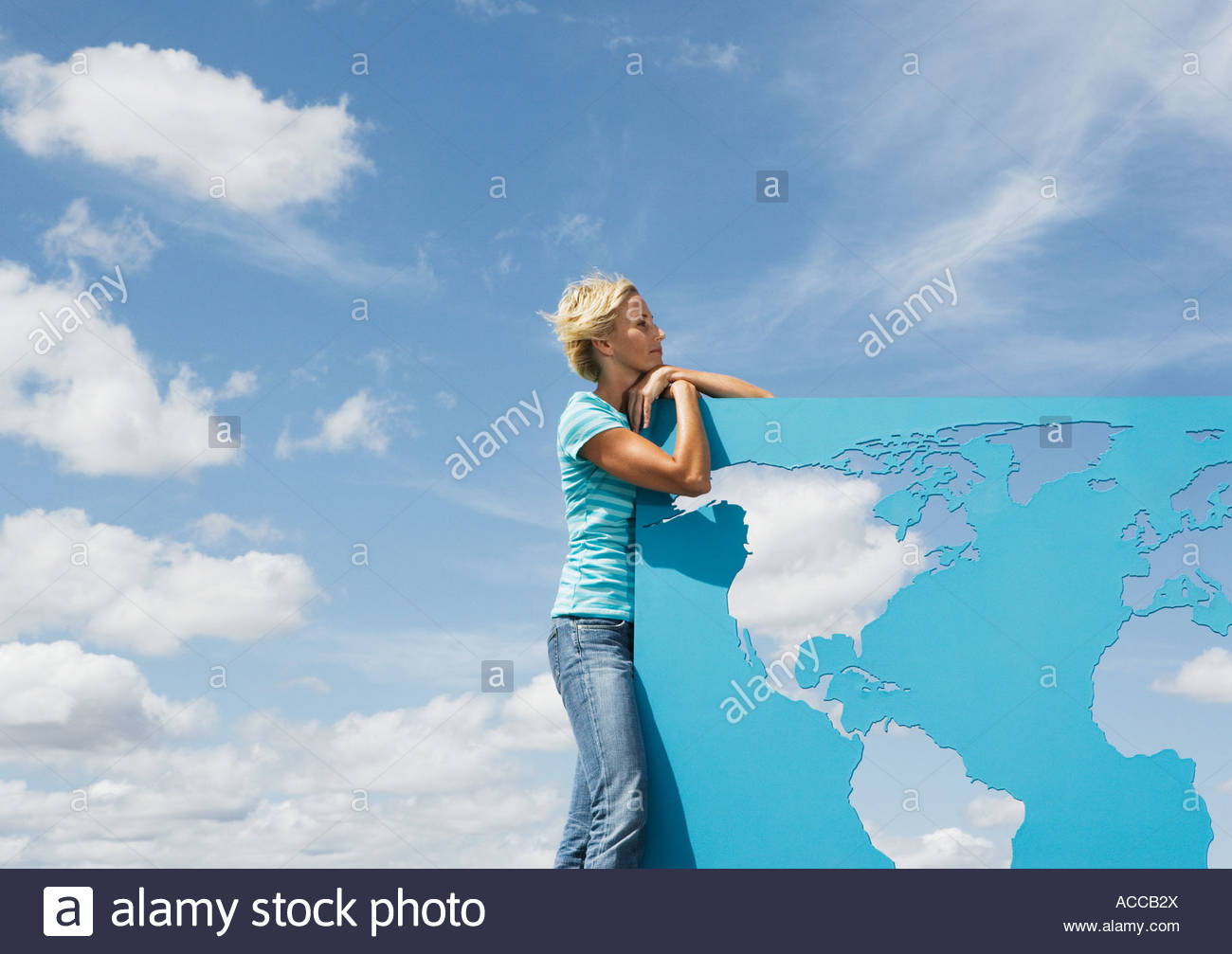 Woman leaning on world map outdoors - Stock Image