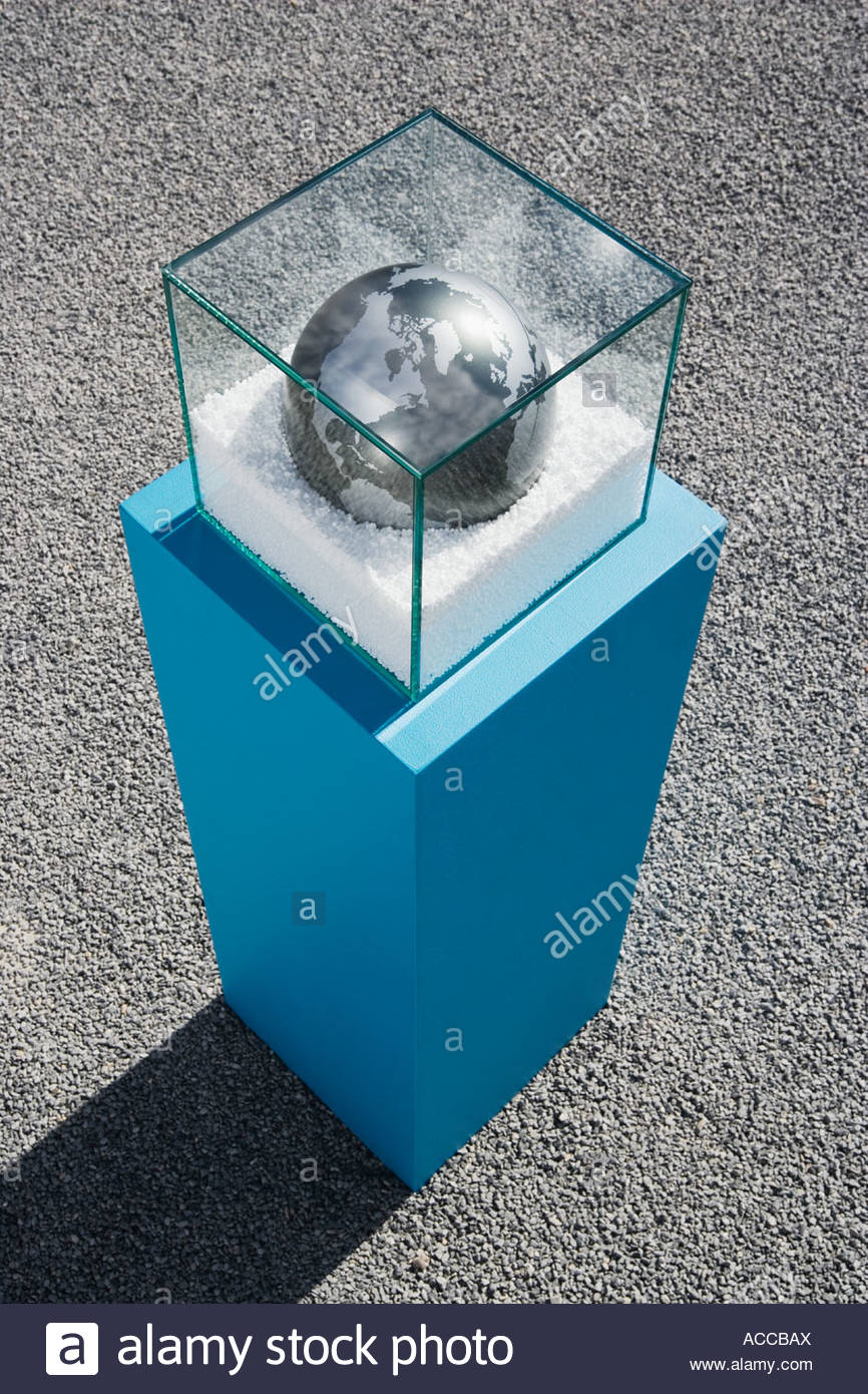 Globe in glass box on pedestal with gravel - Stock Image