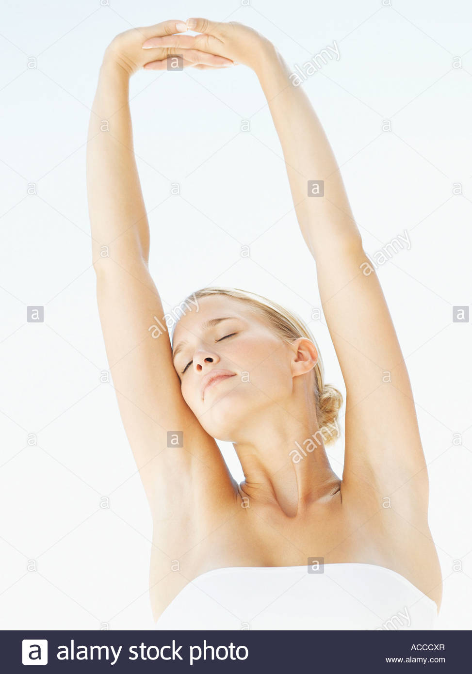 Woman stretching arms upward - Stock Image