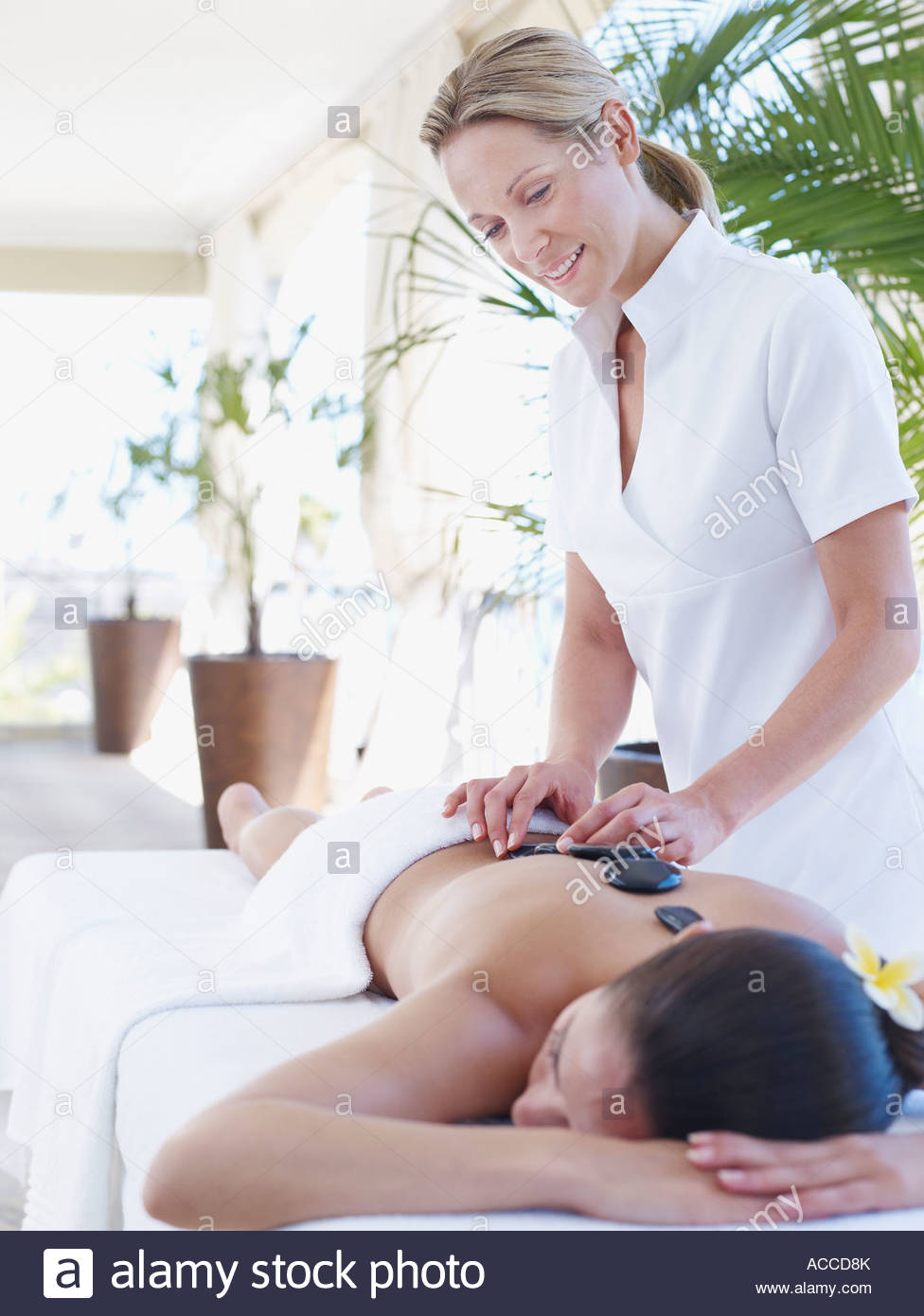 Masseuse placing massage stones on a woman's back - Stock Image
