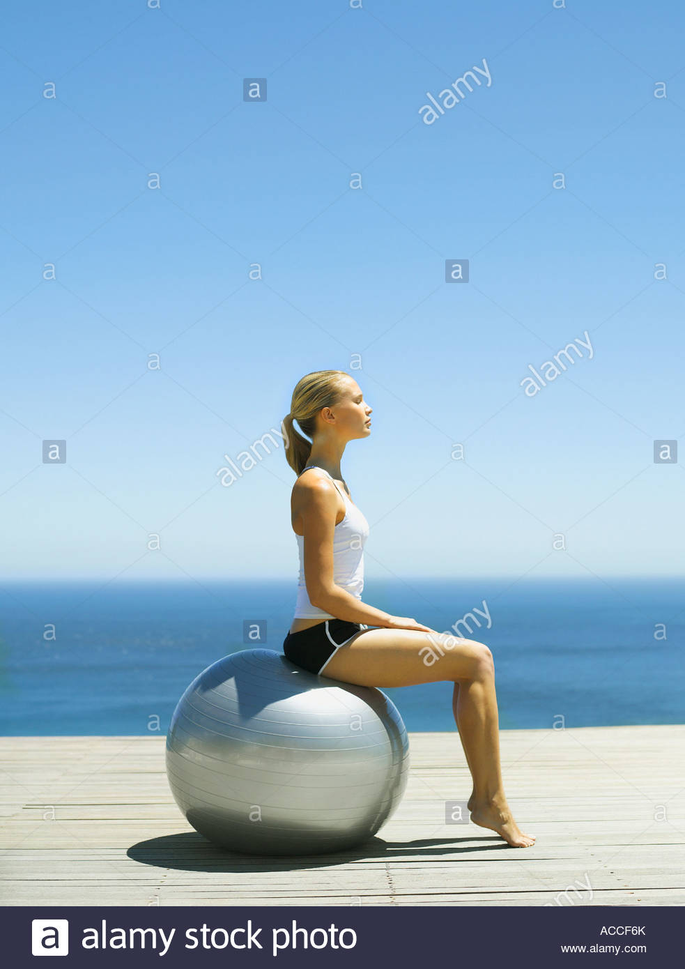 Woman sitting on an exercise ball - Stock Image