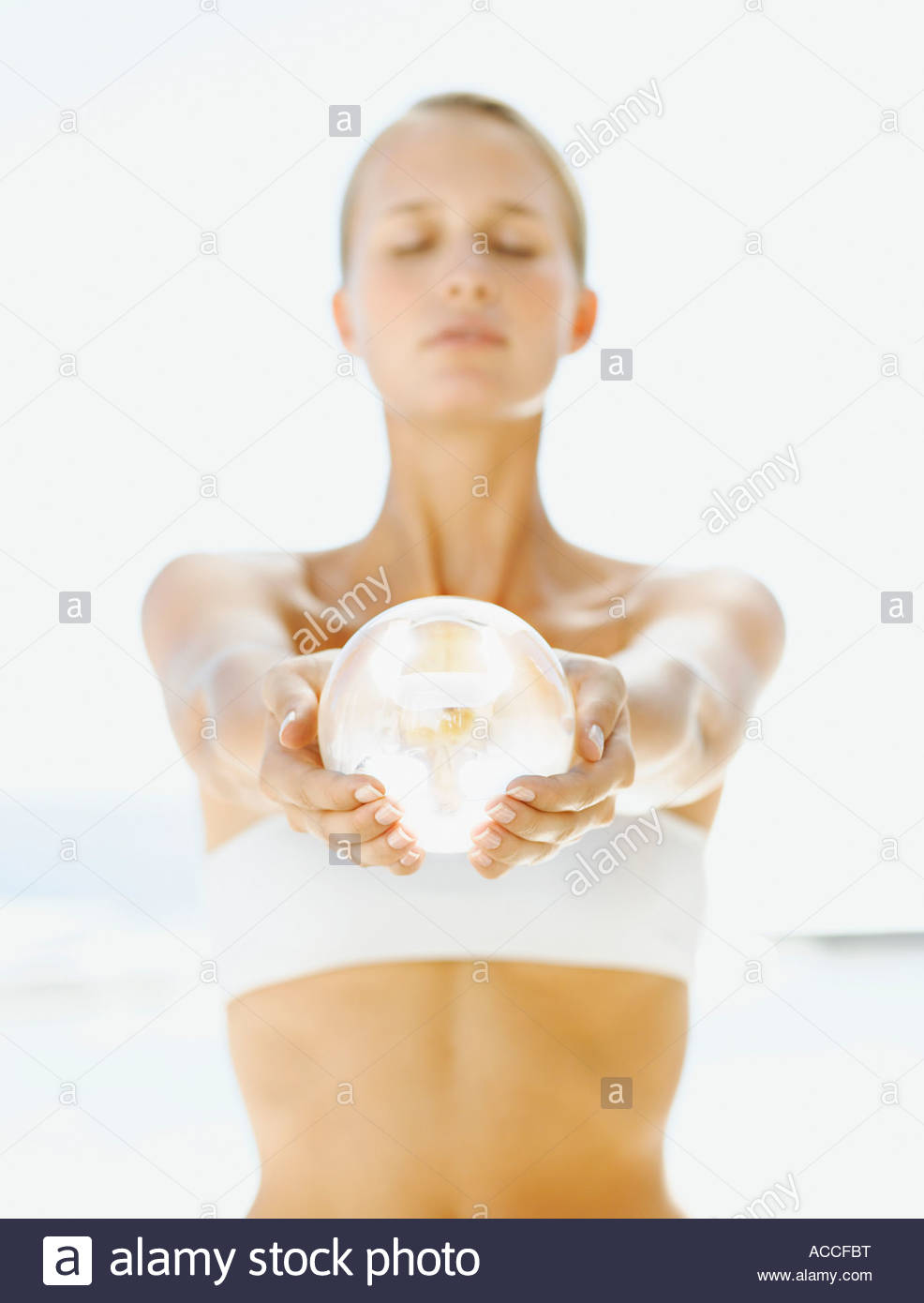 Woman holding an orb forth in her hands - Stock Image