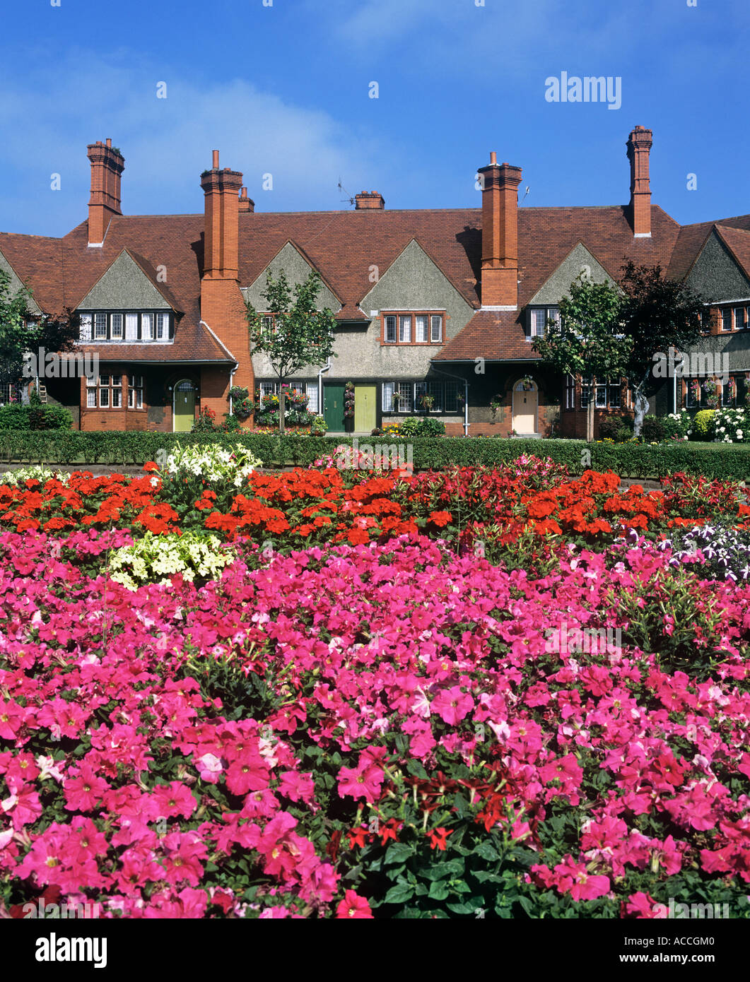 A flower-bedecked traffic roundabout in Port Sunlight, Cheshire, with Arts and Crafts-style housing behind. - Stock Image