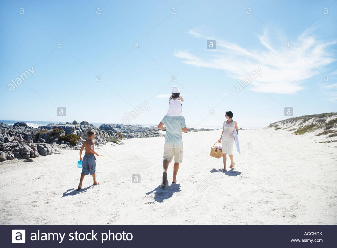 A family going to have a picnic at the beach - Stock Image