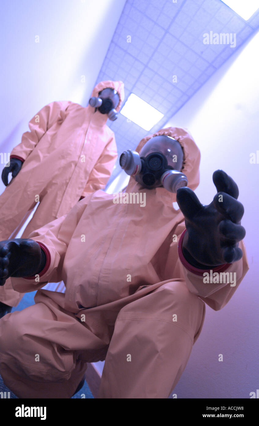 two men wearing NBC biological and chemical protection suits and gas masks - Stock Image