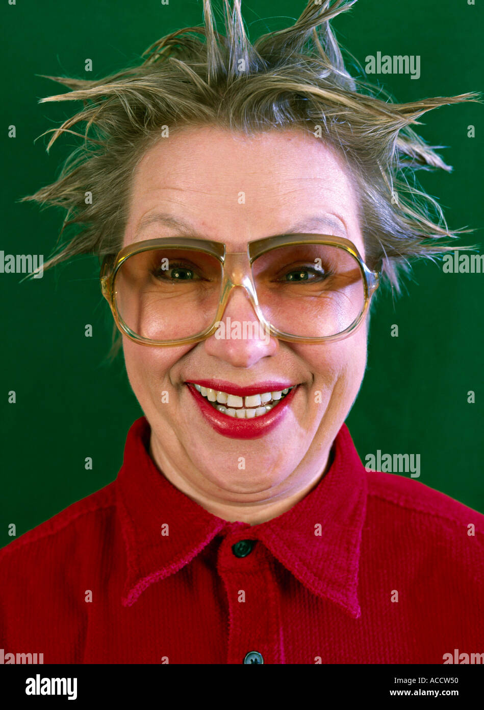 MR woman with tousled hair and big spectacles grinning - Stock Image