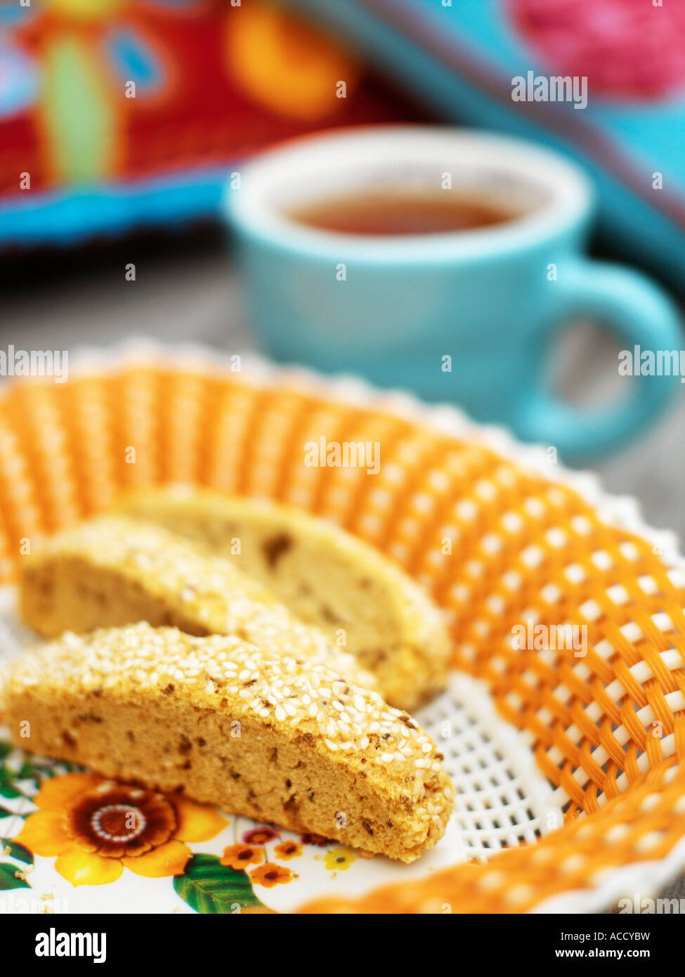 Plate with cookies and a cup in the background. - Stock Image