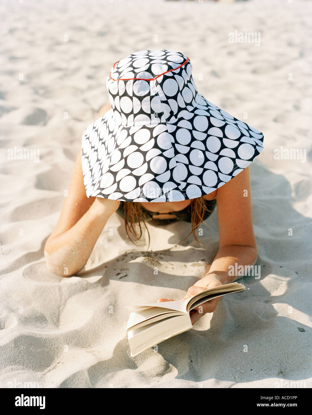 A woman at the beach with a book. - Stock Image