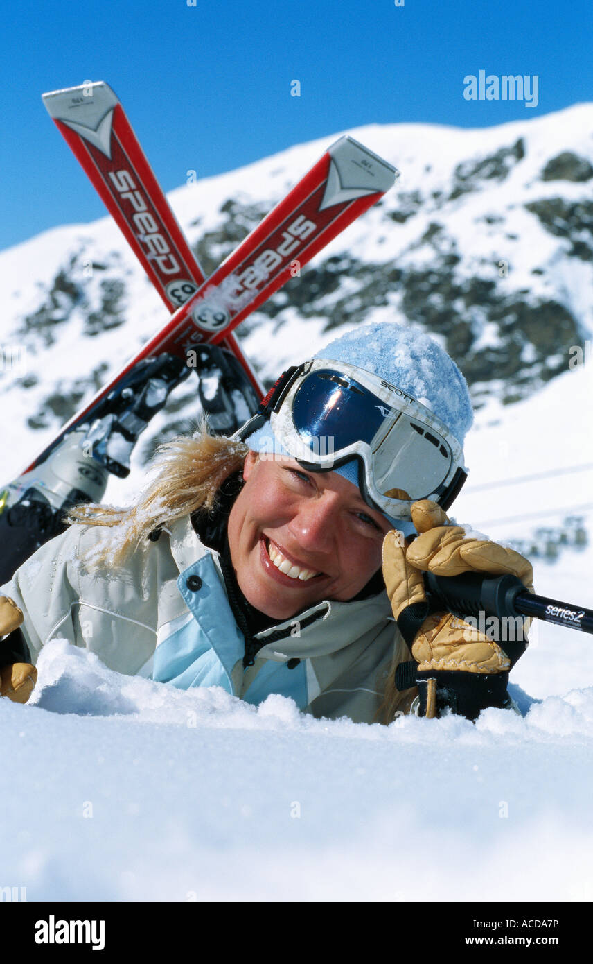 A smiling woman with skiing equipment. - Stock Image