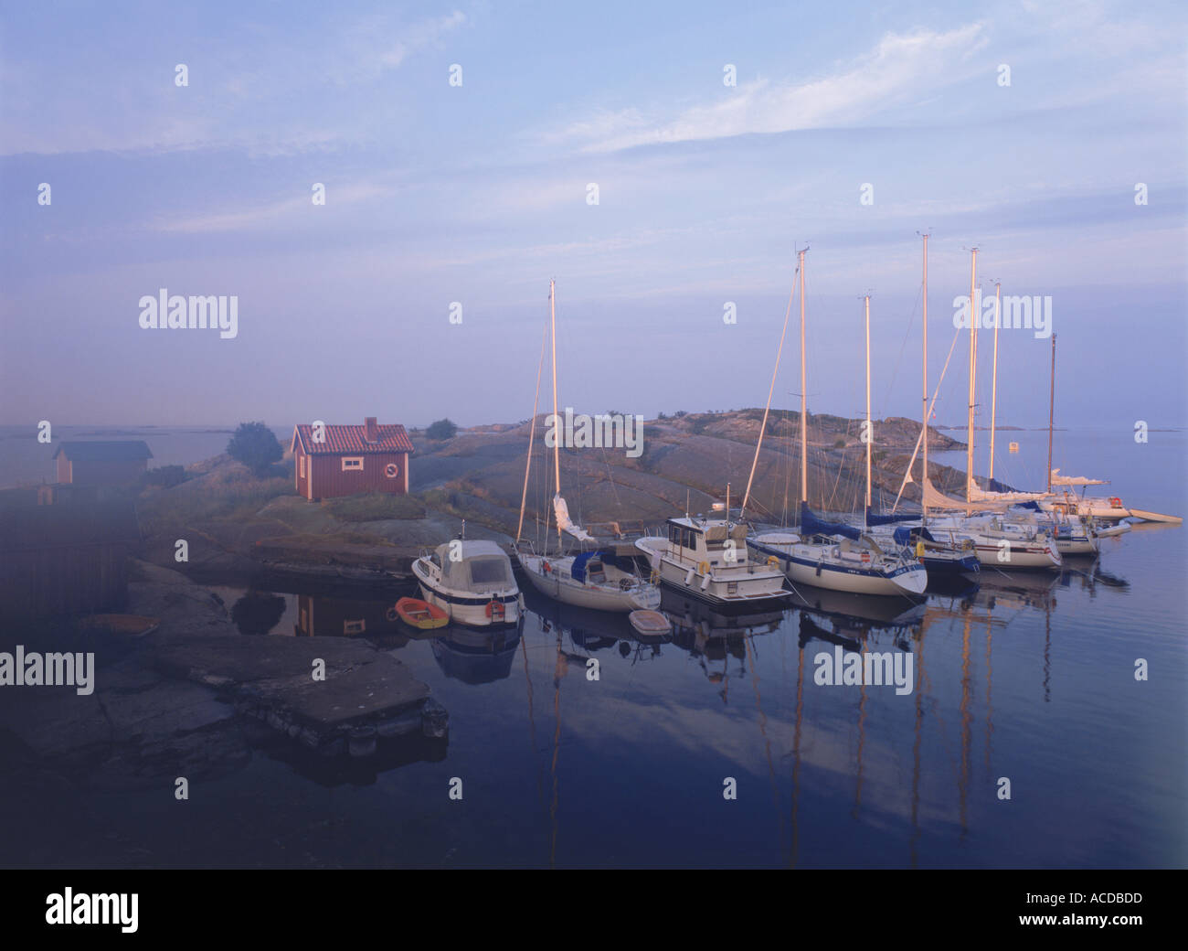 Sailboats anchored at dawn in Stora Nassa island group of Stockholm Archipelago far out into the Baltic Sea - Stock Image