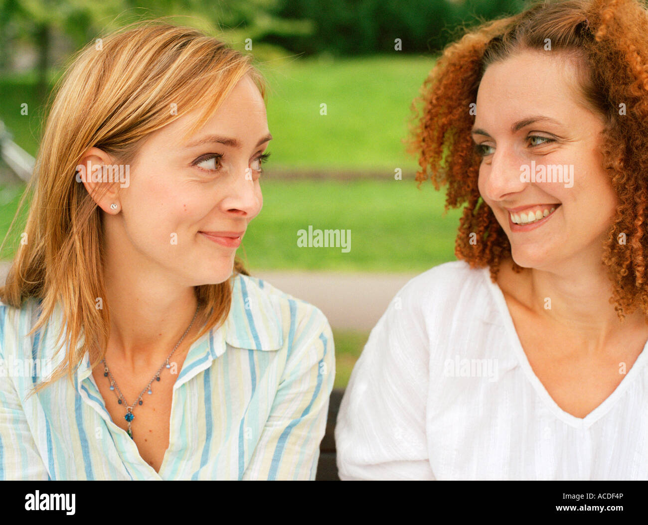 Two smiling women sitting outdoors and looking into each others eyes. - Stock Image
